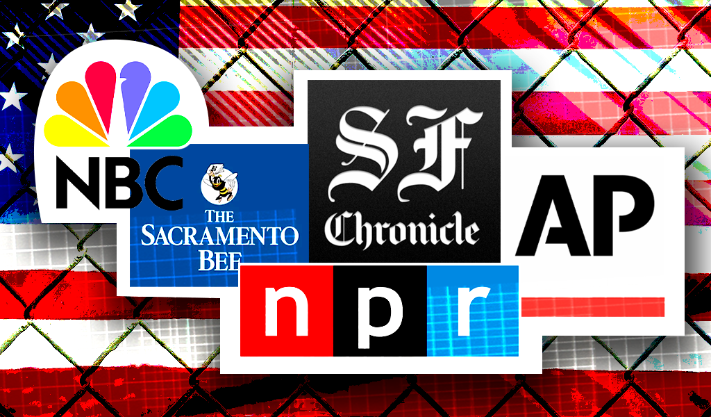 National and local media logos in front of U.S. flag  with chainlink fence