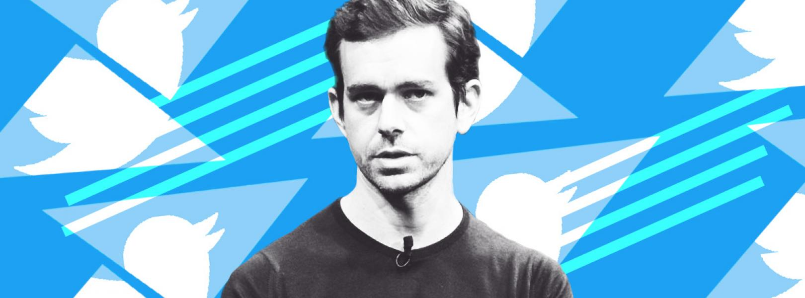 Twitter CEO Jack Dorsey standing in front of Twitter's logo