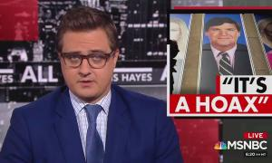 "Chris Hayes with image of Tucker Carlson and chyron reading ""it's a hoax"""