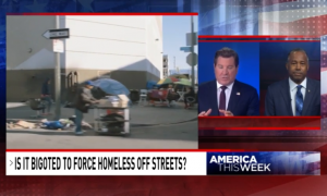 """Footage of tents on sidewalks with smaller window showing split-screen between Eric Bolling and Ben Carson. The chyron reads, """"Is it bigoted to force homeless off streets?"""""""