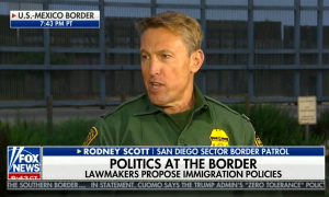 """Former San Diego Sector Border Patrol agent Rodney Scott, in uniform in front of border fencing on The Ingraham Angle in June 2018. Chyron reads """"Politics at the border: Lawmakers propose immigration policies"""""""