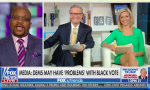 "Fox guest Christopher Harris via satellite on screen left, with Fox & Friends hosts Ainsley Earhardt and Steve Doocy seated in the Fox studios on screen right. Chyron reads ""Media: Dems May Have 'Problem' With Black Vote"""