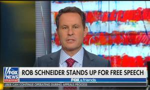 """Brian Kilmeade on a partial US flag background speaking above a chyron reading """"Rob Schneider stands up for free speech"""""""
