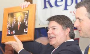 Gregg Jarrett holding a picture of Trump