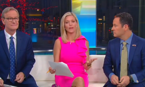 Ainsley Earhardt gesticulating mid-sentence, seated between Steve Doocy on her right and Brian Kilmeade on her left.