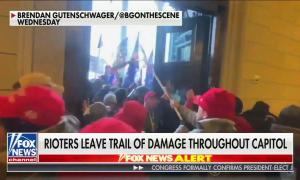 """A Fox News screenshot showing a mob of Trump supporters, many in red MAGA hats, rushing a set of wooden doors in the U.S. Capitol. Chyron reads """"Rioters leave trail of damage throughout Capitol"""""""