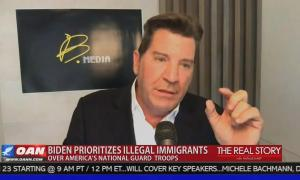 """Former Fox host and Sinclair anchor Eric Bolling appearing on One America News, pinching his fingers together, with chyron reading """"Biden prioritizes illegal immigrants over America's National Guard troops,"""" with a confusingly identical background color to the show logo (The Real Story with Natalie Harp) to the right."""