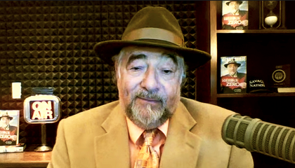 Michael Savage seated in a radio studio, wearing a tan suit and dark brown fedora.