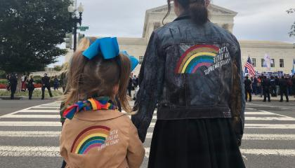 Two people standing in front of the Supreme Court with rainbow jackets