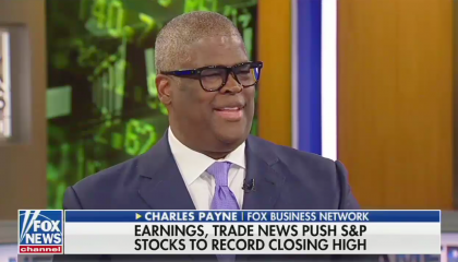 """Charles Payne smiling mid-sentence above a chyron reading """"Earnings, trade news push S&P stocks to record closing high"""""""