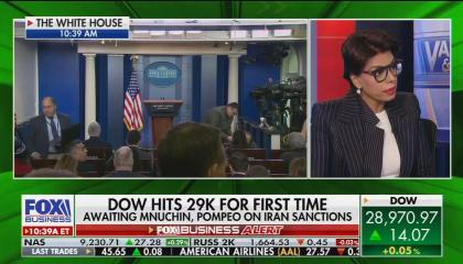 "Fox Business guest Dr. Qanta Ahmed on screen right, with an empty White House podium on screen left, awaiting a press conference. Chyron reads ""Dow hits 29k for first time. Awaiting Mnuchin, Pompeo on Iran sanctions"""