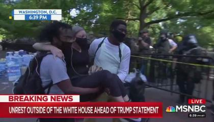 "An MSNBC screenshot of two protesters carrying a third protester, injured during an unprovoked police crackdown. National Guard soldiers are seen in the background. Chyron reads ""Unrest outside White House ahead of Trump statement"""