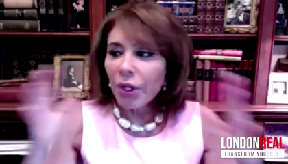 Fox host Jeanine Pirro waving her hands on a webcam, in front of a bookshelf