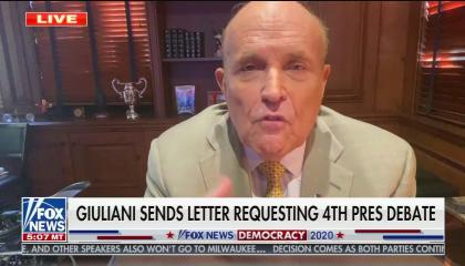 """Rudy Giuliani in a home office with the chyron reading """"Giuliani sends letter requesting 4th pres debate"""""""