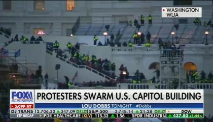 footage of insurrection at the Capitol building; chyron: protesters swarm U.S. capitol building