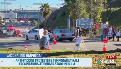 """A screenshot of anti-vaccination demonstrators at the entrance of a mass vaccination site at LA's Dodger Stadium, with a """"Welcome to Dodger Stadium"""" sign visible. Chyron reads """"Anti-vaccine protesters temporarily halt vaccinations at Dodger Stadium in L.A."""""""