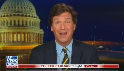 Tucker Carlson in blue checkered shirt and black and yellow tie addresses camera