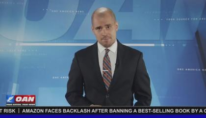 One America News correspondent Pearson Sharp against a relatively plain, OAN-branded light blue background.