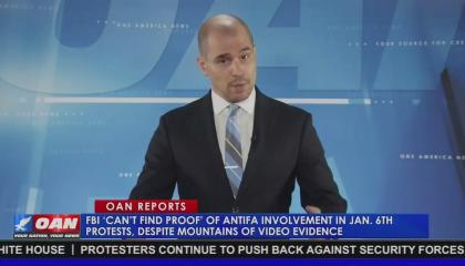 "OAN correspondent Pearson Sharp standing above a chyron reading ""FBI 'can't find proof' of antifa involvement in Jan. 6th protests, despite mountains of video evidence"""