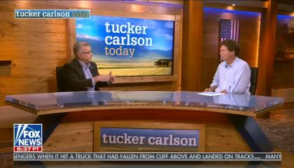 "Tucker Carlson and Hooman Nachalsm sit aross from each other with the show name ""Tucker Carlson Today"" in the background"