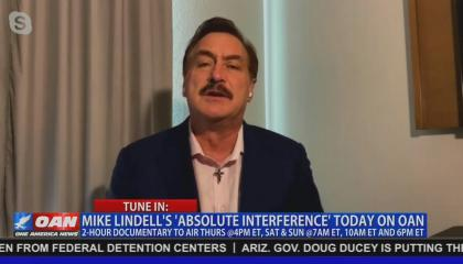 """An OAN screenshot of file footage of MyPillow CEO Mike Lindell. Chyron reads """"Tune in: Mike Lindell's 'Absolute Interference' today on OAN. 2-hour documentary to air Thurs @4PM ET, Sat & Sun @7AM ET, 10AM ET and 6PM ET"""""""