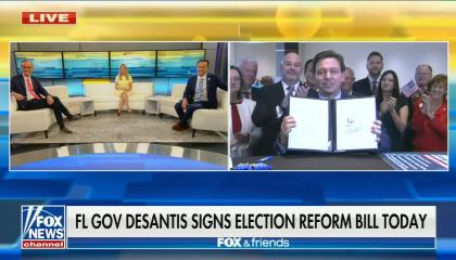 """A Fox & Friends split screen with the hosts on a curvy couch on screen left, and on screen right is Florida Governor RonDeSantis holding up an election law, SB 90, he signed live on Fox & Friends. DeSantis supporters are cheering behind him. Chyron reads """"FL Gov DeSantis signs election reform bill today"""""""