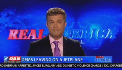 """OAN host Dan Ball in studio above a chyron reading """"Dems Leaving On A Jetplane"""""""