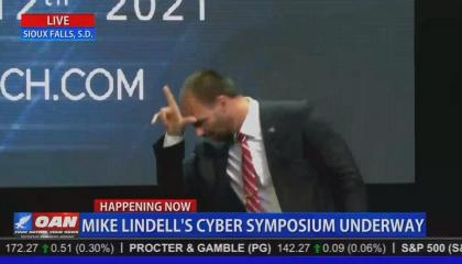 """An OAN screenshot of Eduardo Bolsonaro, third son of Brazilian President Jair Bolsonaro, at Mike Lindell's election fraud cyber symposium, holding his thumb and index finger in an L-shape on his forehead, for """"loser."""" Chyron reads """"Mike Lindell's cyber symposium underway"""""""