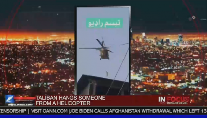 """A screenshot from a video with a helicopter in midair from the OAN show In Focus with Stephanie Hamill. The chyron reads """"Taliban hangs someone from a helicopter"""""""