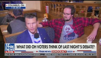 "Pete Hegseth sitting on the left-hand side of a restaurant booth, looking off to the left side of the screen, next to a man in a red flannel and gray Obama-style 'Hope"" t-shirt displaying Edith Espinal's face and the name ""EDITH"""
