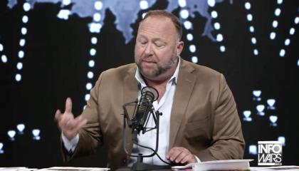 Screenshot of Alex Jones gesturing and sitting behind the desk on his InfoWars set