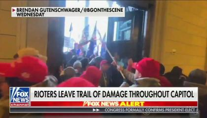 "A Fox News screenshot showing a mob of Trump supporters, many in red MAGA hats, rushing a set of wooden doors in the U.S. Capitol. Chyron reads ""Rioters leave trail of damage throughout Capitol"""