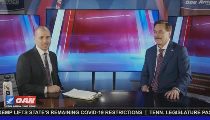 OAN correspondent Pearson Sharp and MyPillow CEO Mike Lindell sitting at an unbranded news desk, waiting after an interview