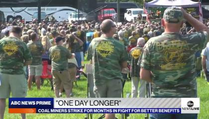 """protestors in United Mine Workers of America shirts standing at a rally with an ABC News banner at the bottom reading """"one day longer"""""""