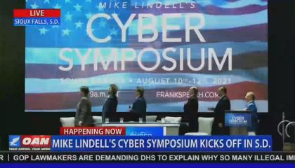 """Screenshot of an OAN broadcast of MyPillow CEO Mike Lindell and a panel pledging allegiance to a large American flag video, mid-transition from a screen reading """"Mike Lindell's Cyber Symposium."""" OAN chyron reads """"Mike Lindell's Cyber Symposium Kicks Off In S.D."""""""