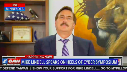 """An OAN screenshot of MyPillow CEO Mike Lindell on """"Lindell TV"""", with a folded U.S. flag behind his right shoulder, and an airbrushed portrait of Jesus Christ and a lion behind his left shoulder. Chyron reads """"Mike Lindell speaks on heels of cyber symposium"""""""