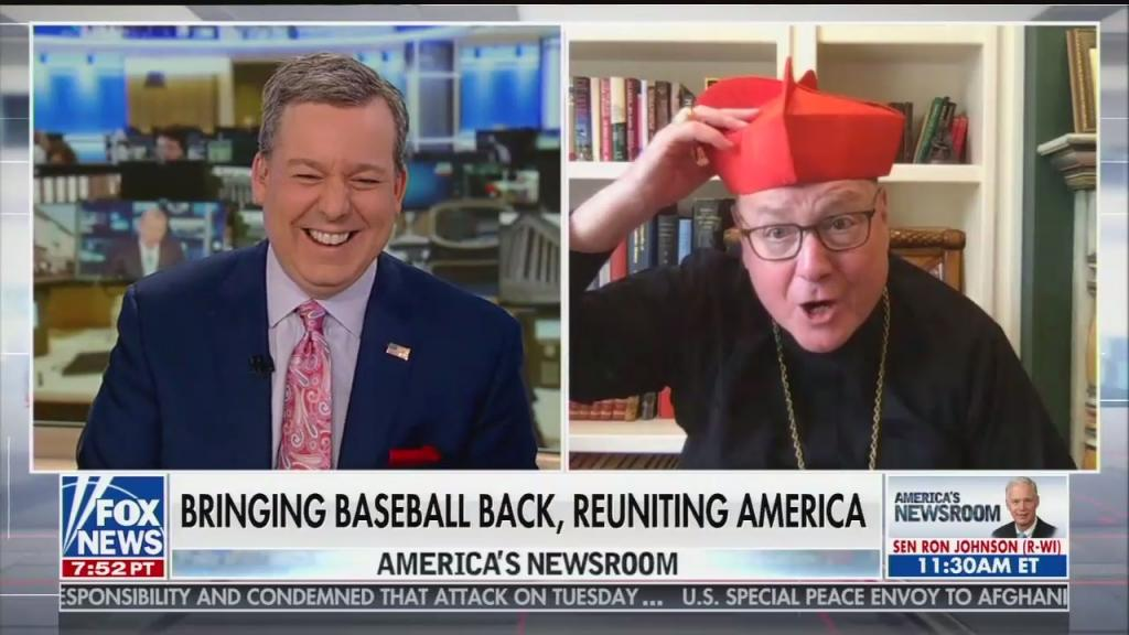 "Anchor Ed Henry laughing at Cardinal Timothy Dolan, Archbishop of New York, comically putting on a hat. Chyron reads ""Bringing baseball back, reuniting America"""